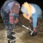 Ice Stupa team working with icy water sprinkler systems late at night.